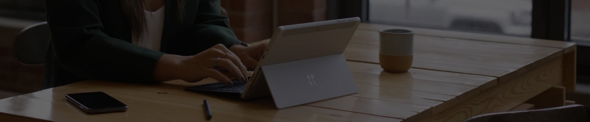 Darkened image of a person using a Surface Pro in laptop mode.