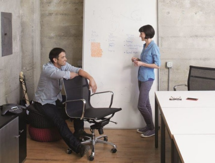 Two people casually talking in an office.