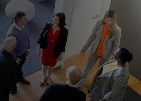 Six people standing talking to each other in an office.