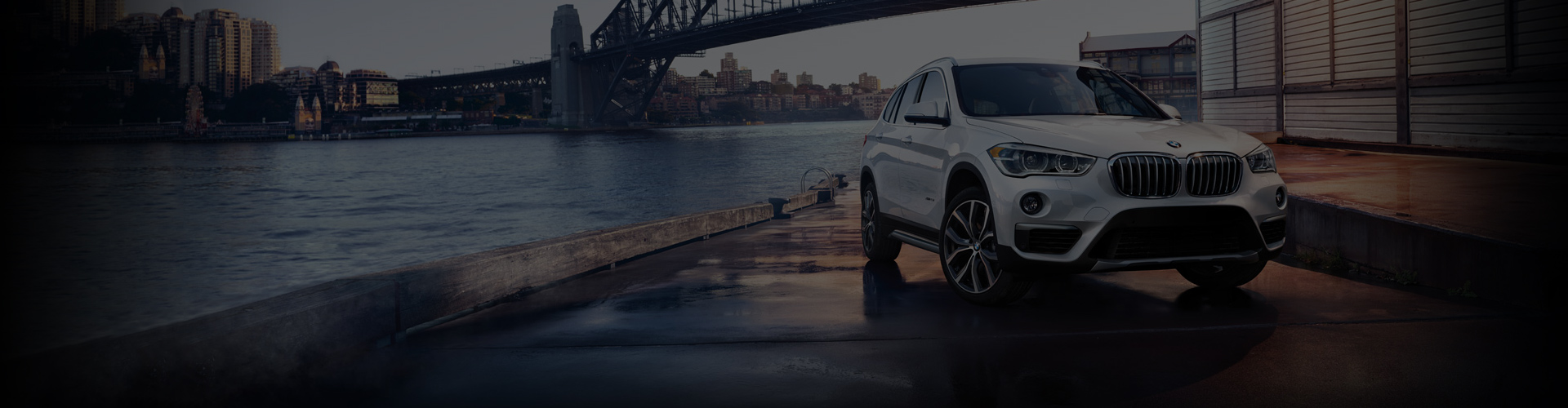 White BMW SUV on river dock with water and bridge.