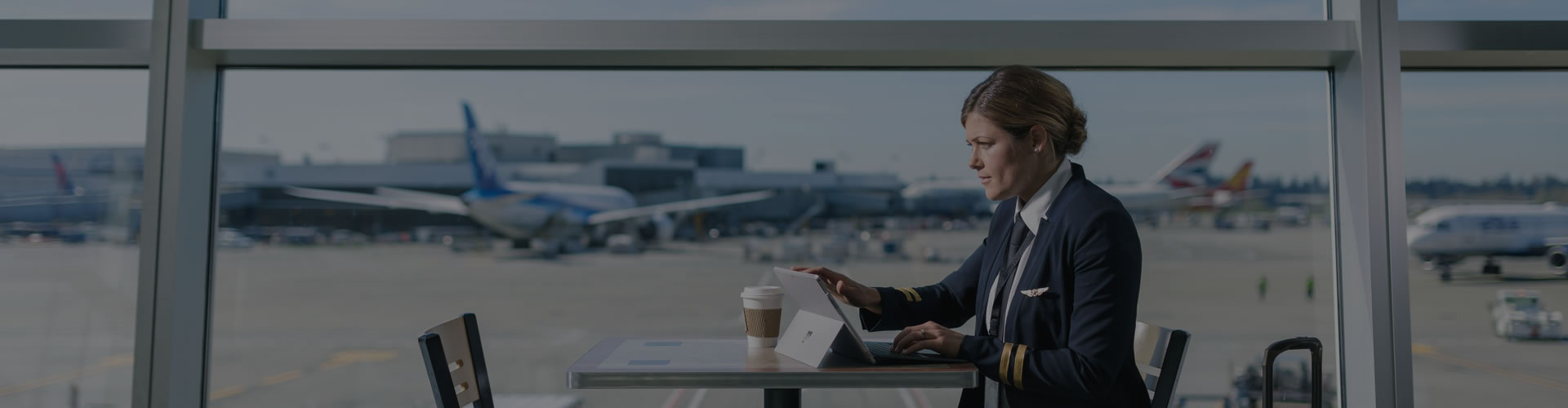 Image of a woman using a tablet at an airport