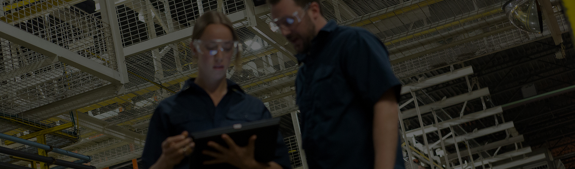 Factory workers looking at tablet device.