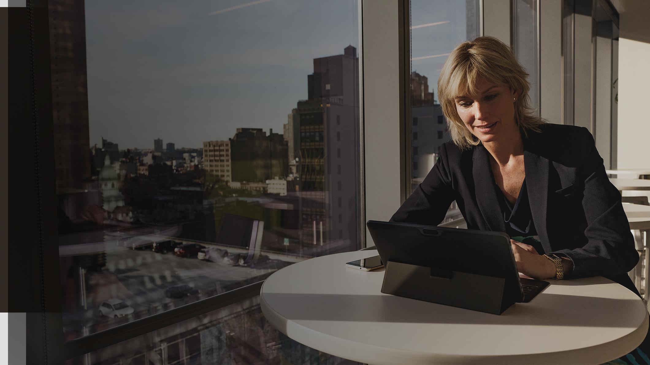 O femeie stă la un birou cu un dispozitiv