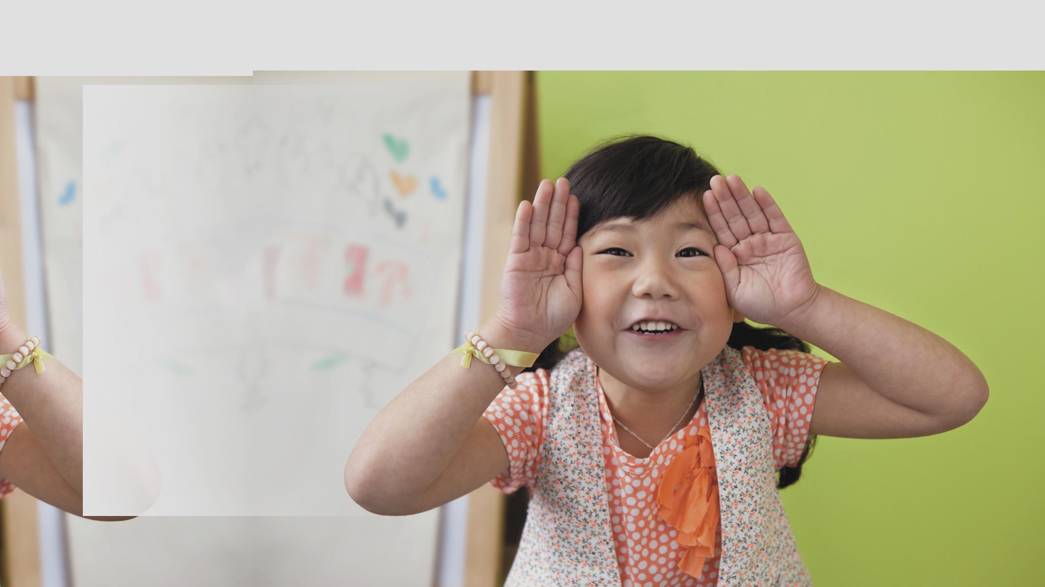 Una niña sonriendo con las manos cerca de la cara