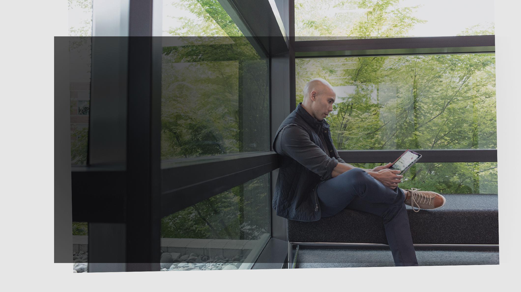 Vīrietis sēž uz soliņa un skatās uz ierīci rokās