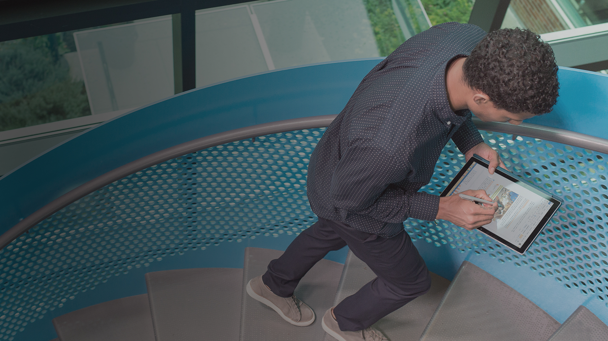 A man works on a tablet while walking up a stairwell