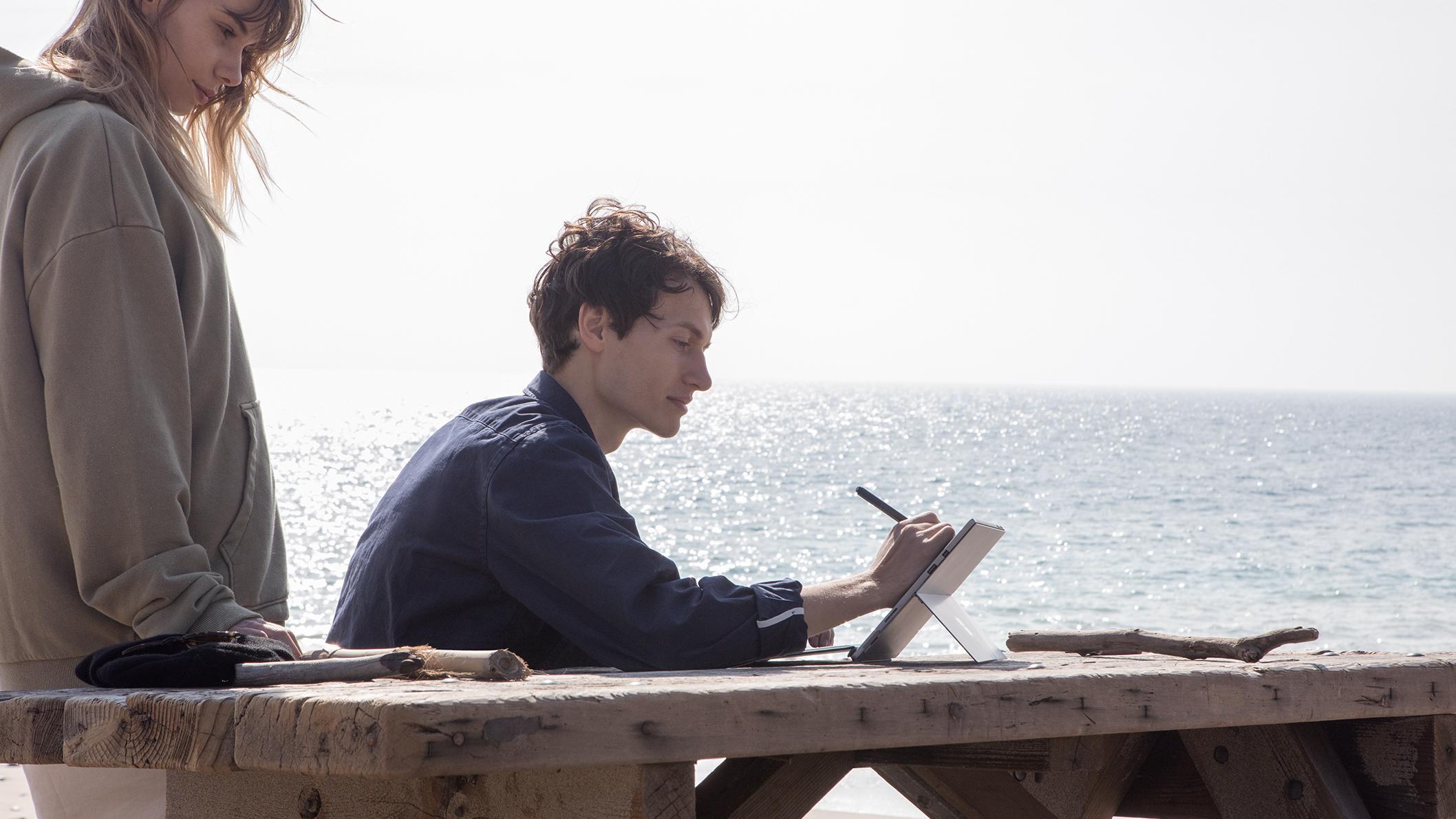 Hombre en la mesa escribiendo en la pantalla Surface Pro con Surface Pen