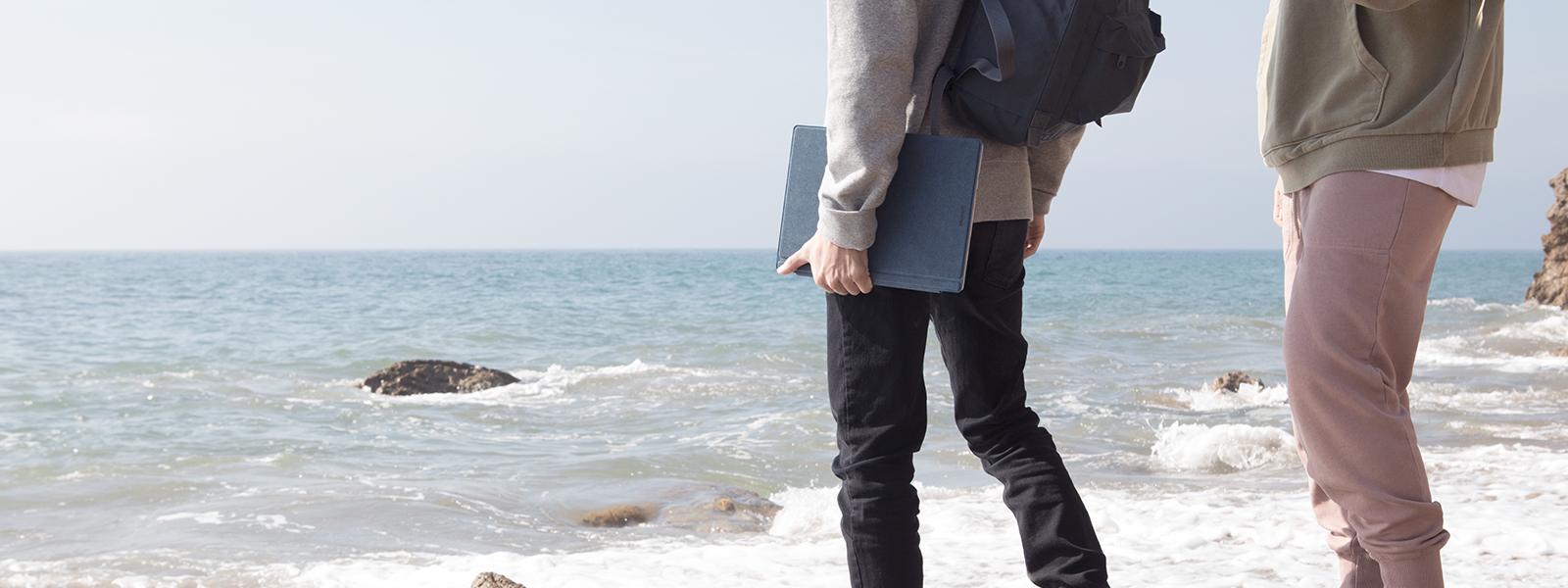 Dos personas en la playa, una con Surface Pro