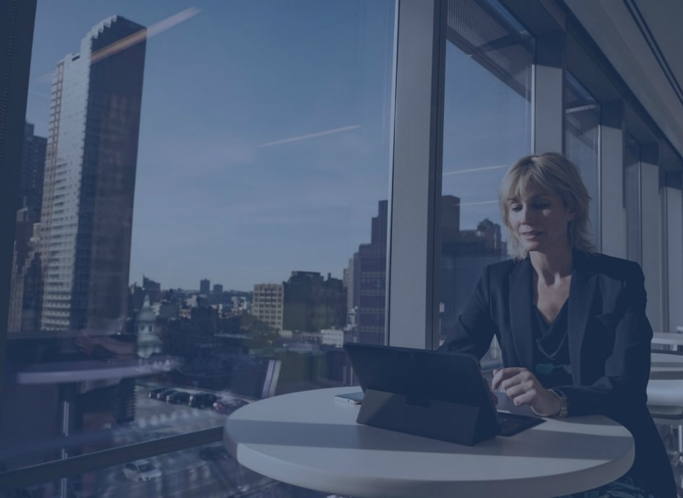 Image of a woman on a laptop with a view of skyscrapers.