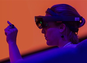 Woman with VR goggles pointing at screen.