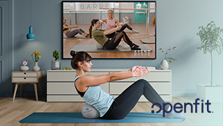 Woman in a live work out session performing abdominal crunches from her living room, which includes a TV, sideboard, table, and plants