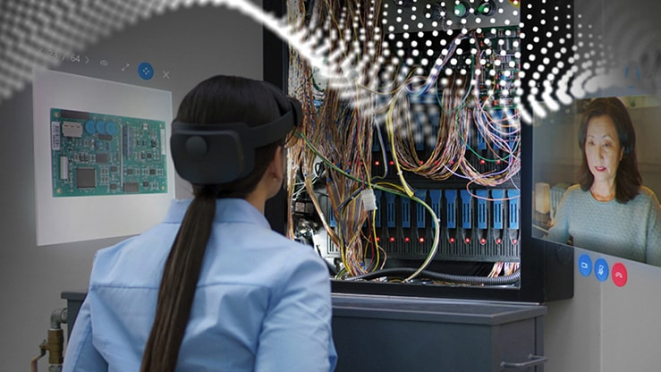 A person wearing HoloLens looking at a machine and screens in AR.