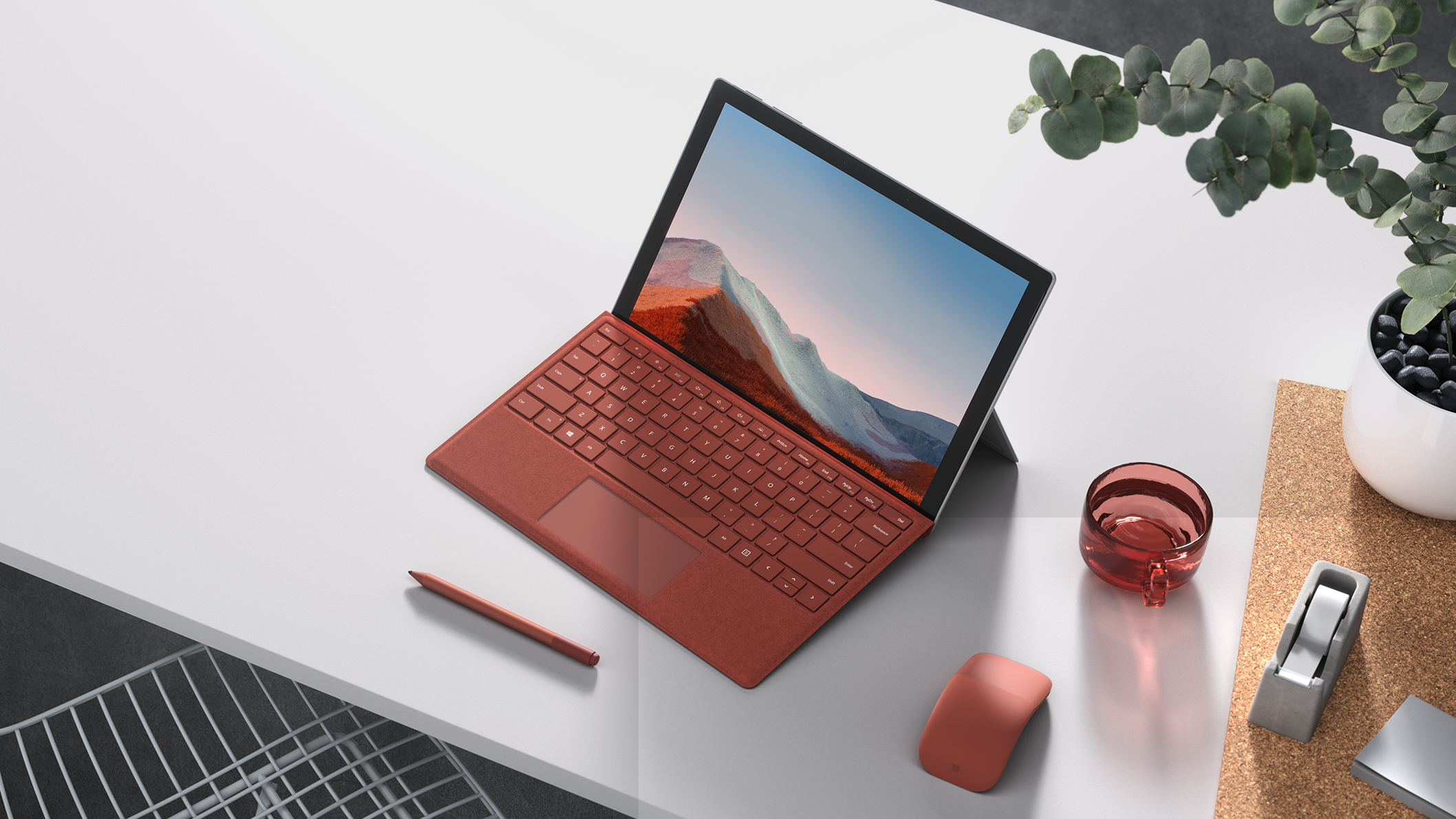 A Surface Pro 7+ in laptop mode with poppy red typepad on a desk.