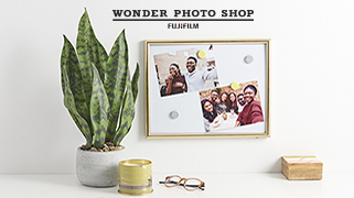 A desk with a plant and other items on it with photos pinned to a board beneath the words Wonder Photo Shop FUJIFILM