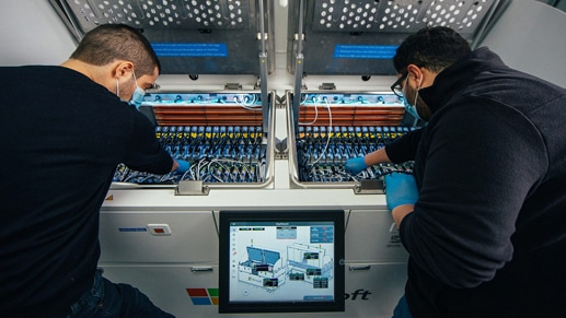 Two employees working on a datacenter server.