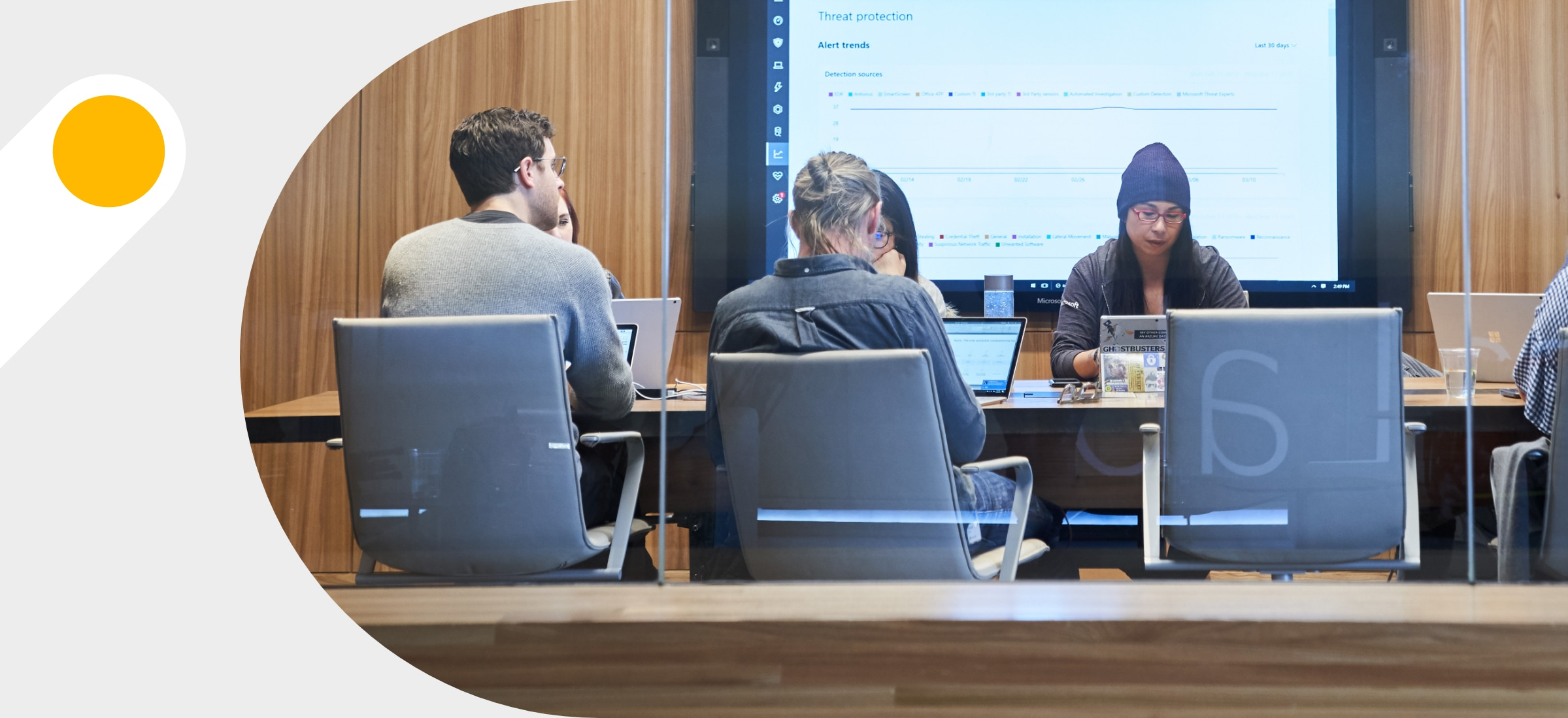 A meeting with 7 people in a conference room with a large screen on the back wall displaying notes in Teams.