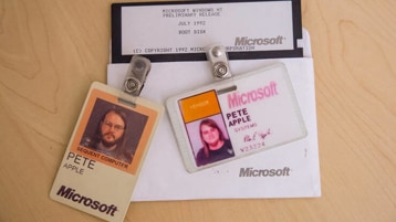 Collection of old two early Microsoft badges and a Windows boot disk from when Apple first started working at Microsoft.