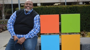 Dwight Jones sits next to the Microsoft sign on the edge of the Microsoft campus. He is smiling.