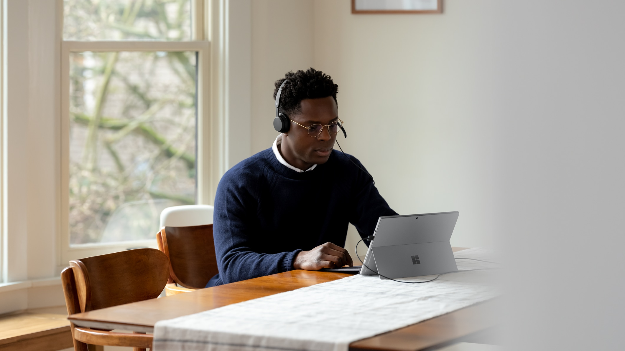 A person with the Microsoft Modern USB Headset for Business plugged into a Surface device.