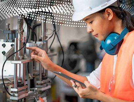 A person wearing PPE holding a tablet and operating a large piece of machinery.