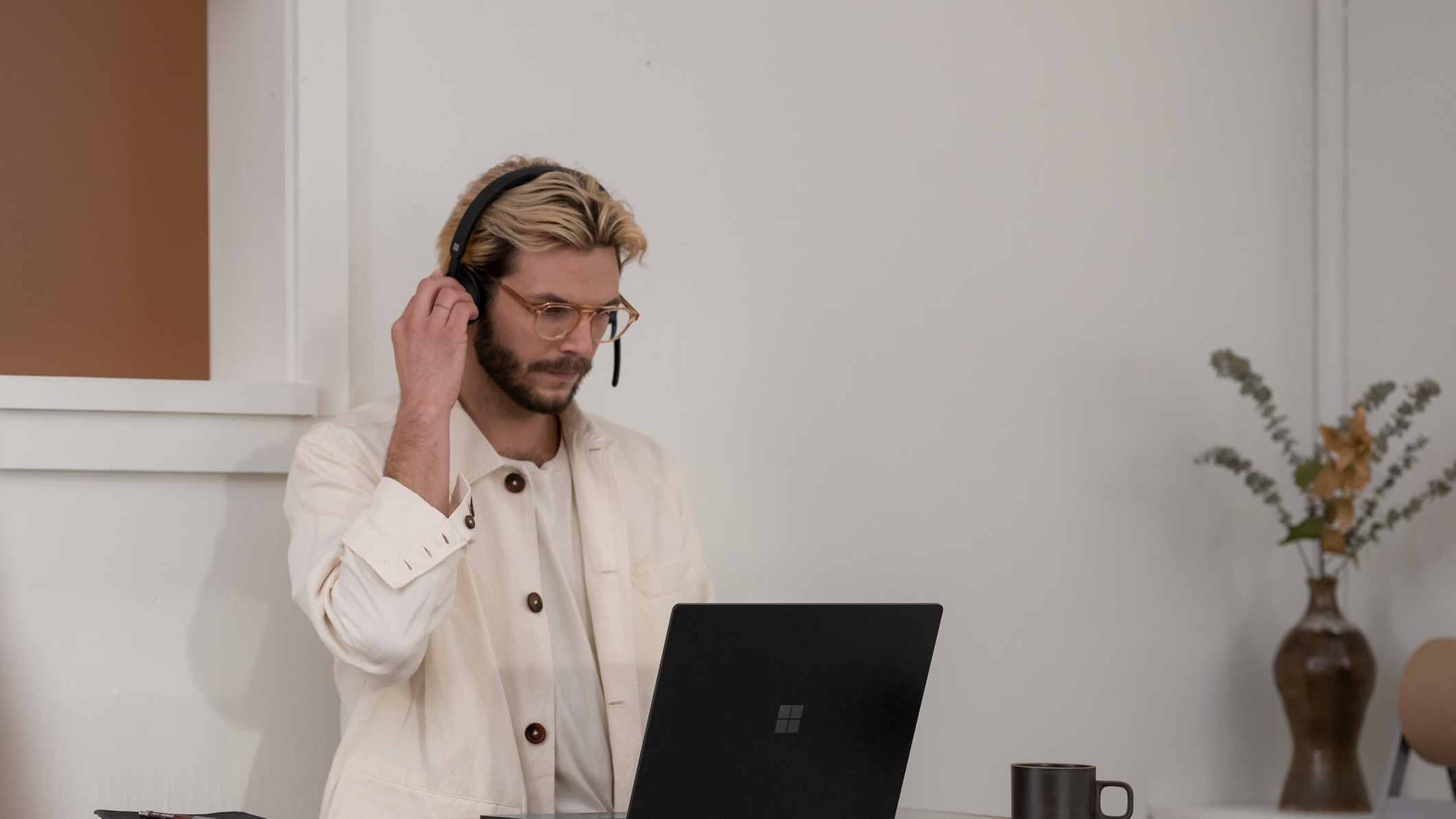 A person uses an Microsoft Modern Wireless Headset for Business while looking at a device.