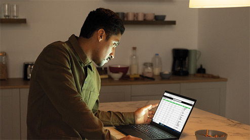 Image of a man working on a laptop in a kitchen.
