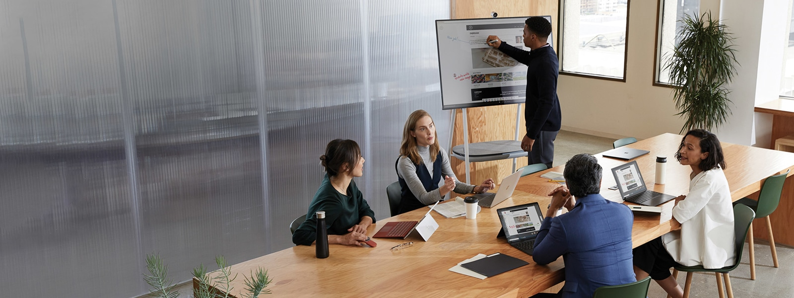 Co-workers collaborating with Surface laptops in a modern conference room.