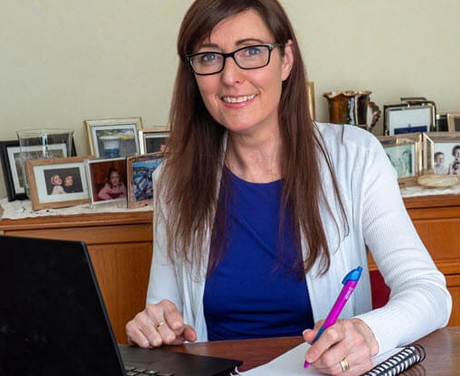 Tait, wearing glasses and a white sweater, sits at a wood desk with her laptop open and a notepad at the ready.