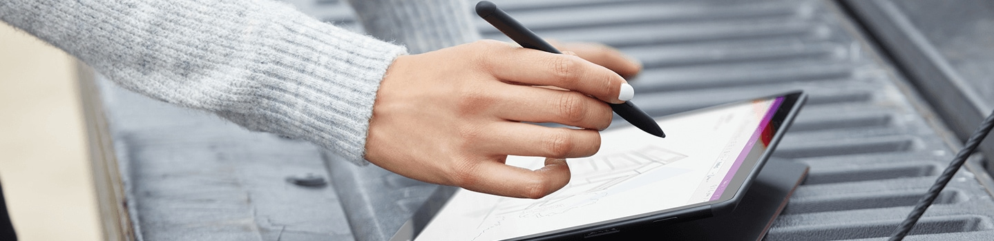 A hand using a pen to write on a tablet.