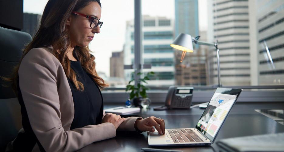 Bir ofiste oturarak dizüstü bilgisayar kullanan bir kişi.
