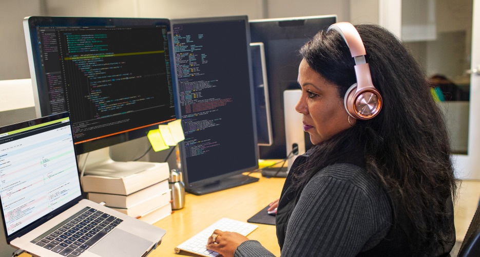 A person wearing headphones using a laptop that is connected to multiple monitors.