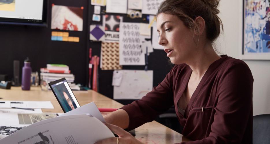Dizüstü bilgisayarında Teams görüntülü görüşmesi yaparken evraklara bakan kişi.