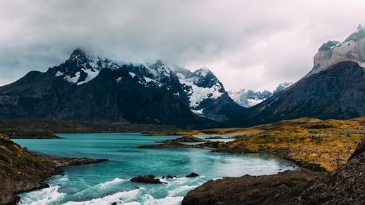 A flowing body of water surrounded by snow-capped mountains