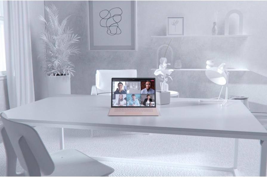 Teams görüntülü görüşmesi görüntülenen bir dizüstü bilgisayar bulunan yemek odası masası.