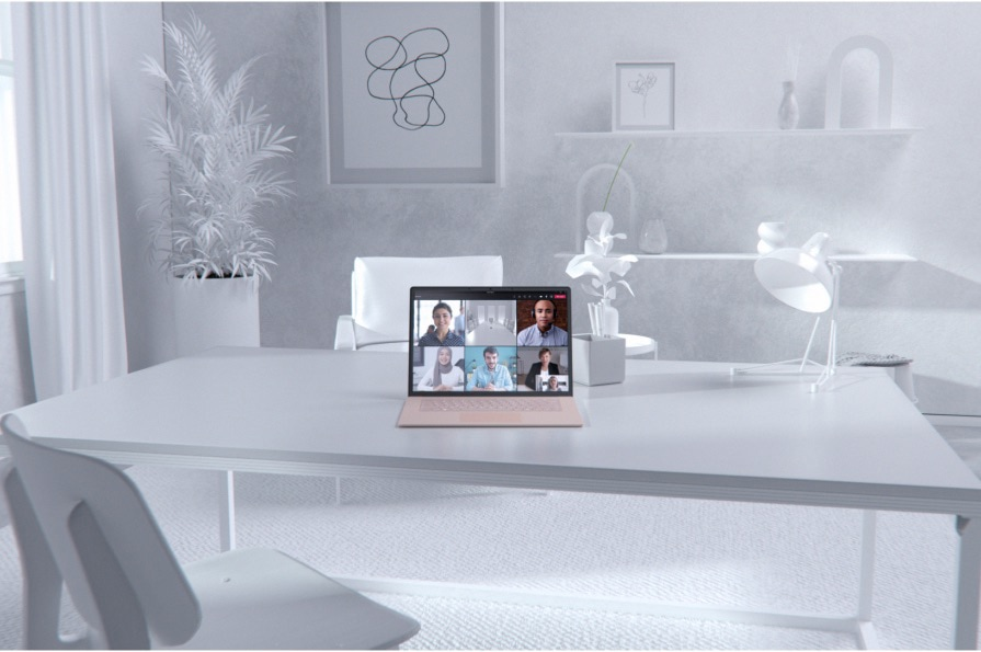 A dining room table with a laptop displaying a Teams video call.