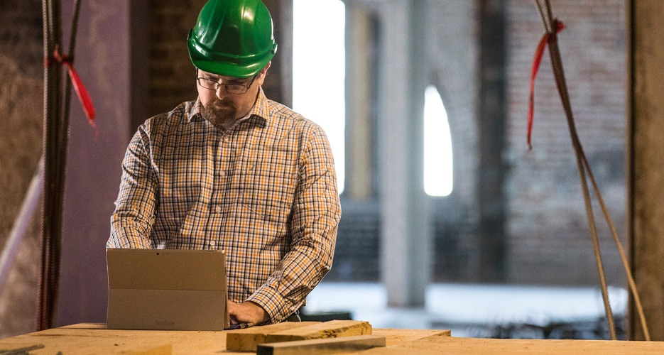 A person wearing a hard hat and using a tablet.