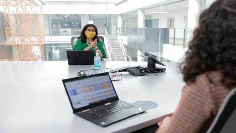 Zwei Frauen sitzen sich in einem Konferenzraum gegenüber. Eine Frau trägt dabei eine Maske