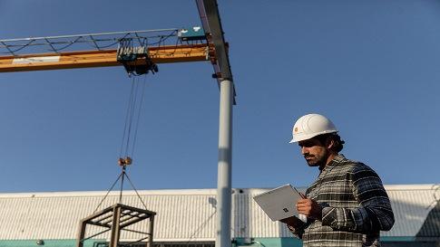 Mann mit Tablet in der Hand auf einem Industriegelände