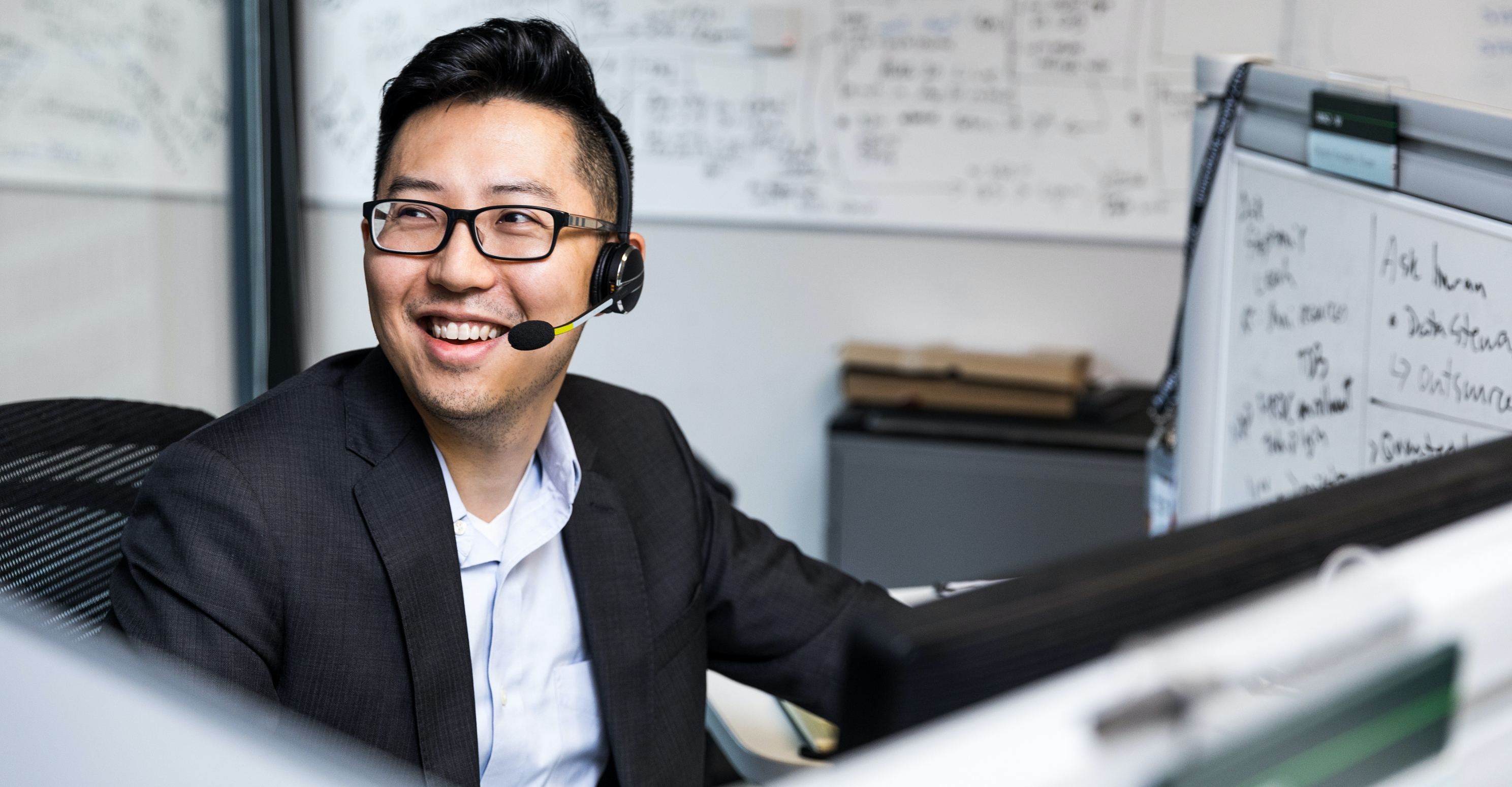 A person smiling while wearing a headset and working at their desk.