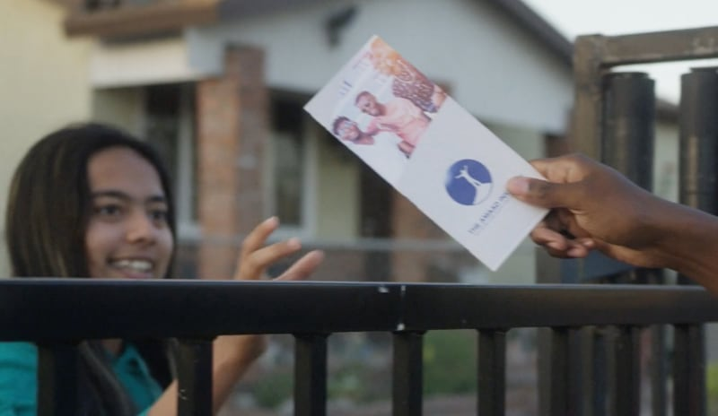 A person being handed a pamphlet over a fence.