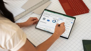 An adult female at work using Surface Pro with Excel open.
