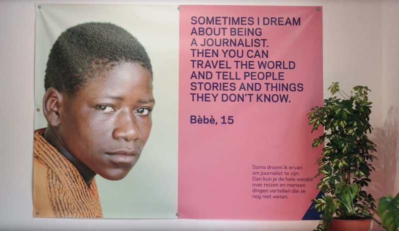 A wall tapestry with an image of a child named Bèbè and a quote from them talking about their dream of being a journalist.