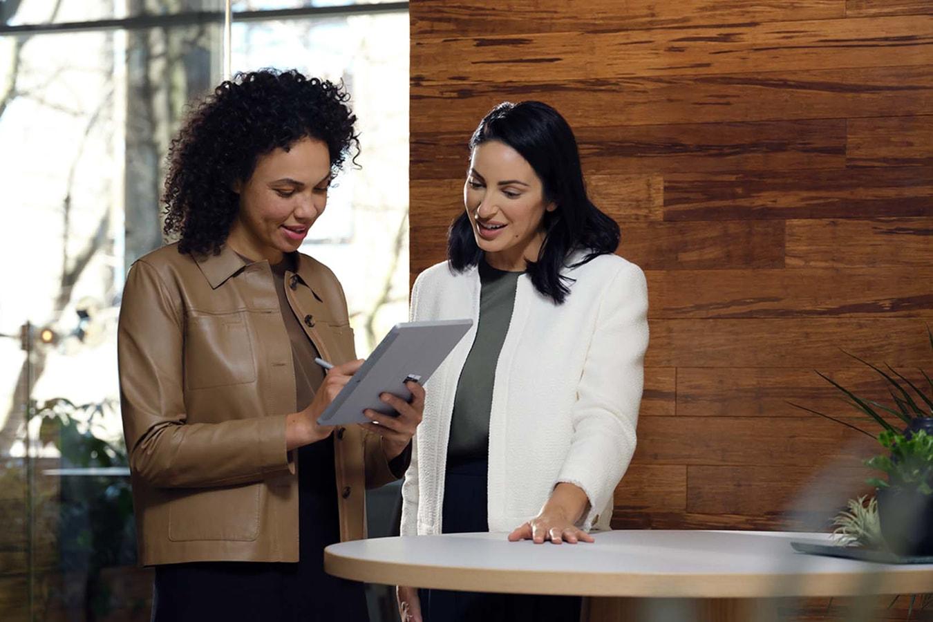 Kaksi työtoveria tekee yhteistyötä Surface Go 3 -laitteen parissa toimistossa