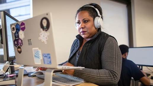 A person sitting in an office working at their desk with headphones on.