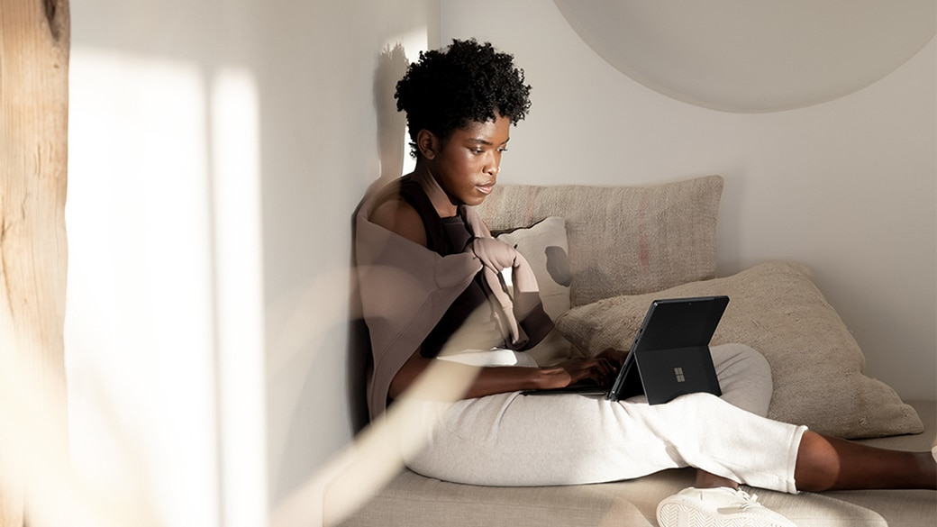 A person relaxing with Surface Pro 8 in kickstand mode.