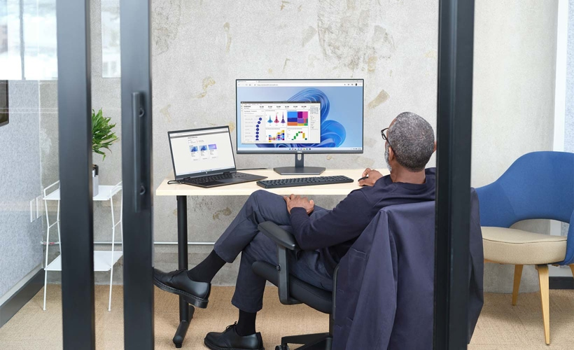 A person sitting in a glass office using a laptop connected to a desktop monitor.