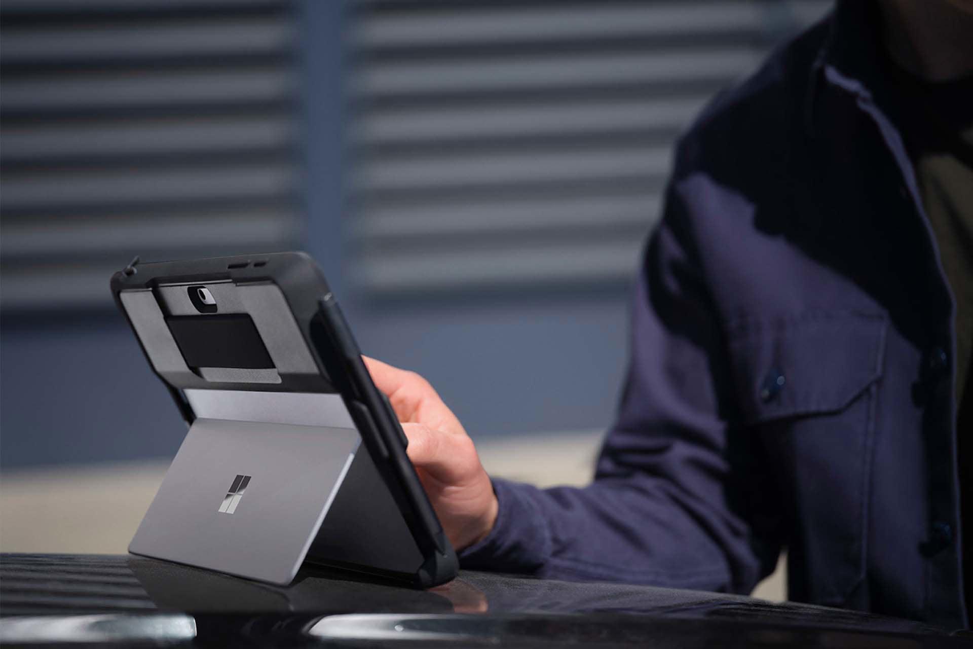 Henkilö koskettaa kotelossa olevaa Surface Go 3 -laitetta