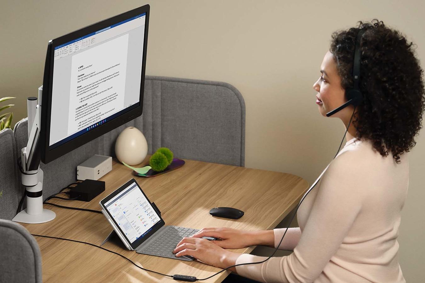 Henkilö työskentelee toimistossa Surface Go 3 -laitteella, johon on yhdistetty Surface Dock 2 ja ulkoinen näyttö