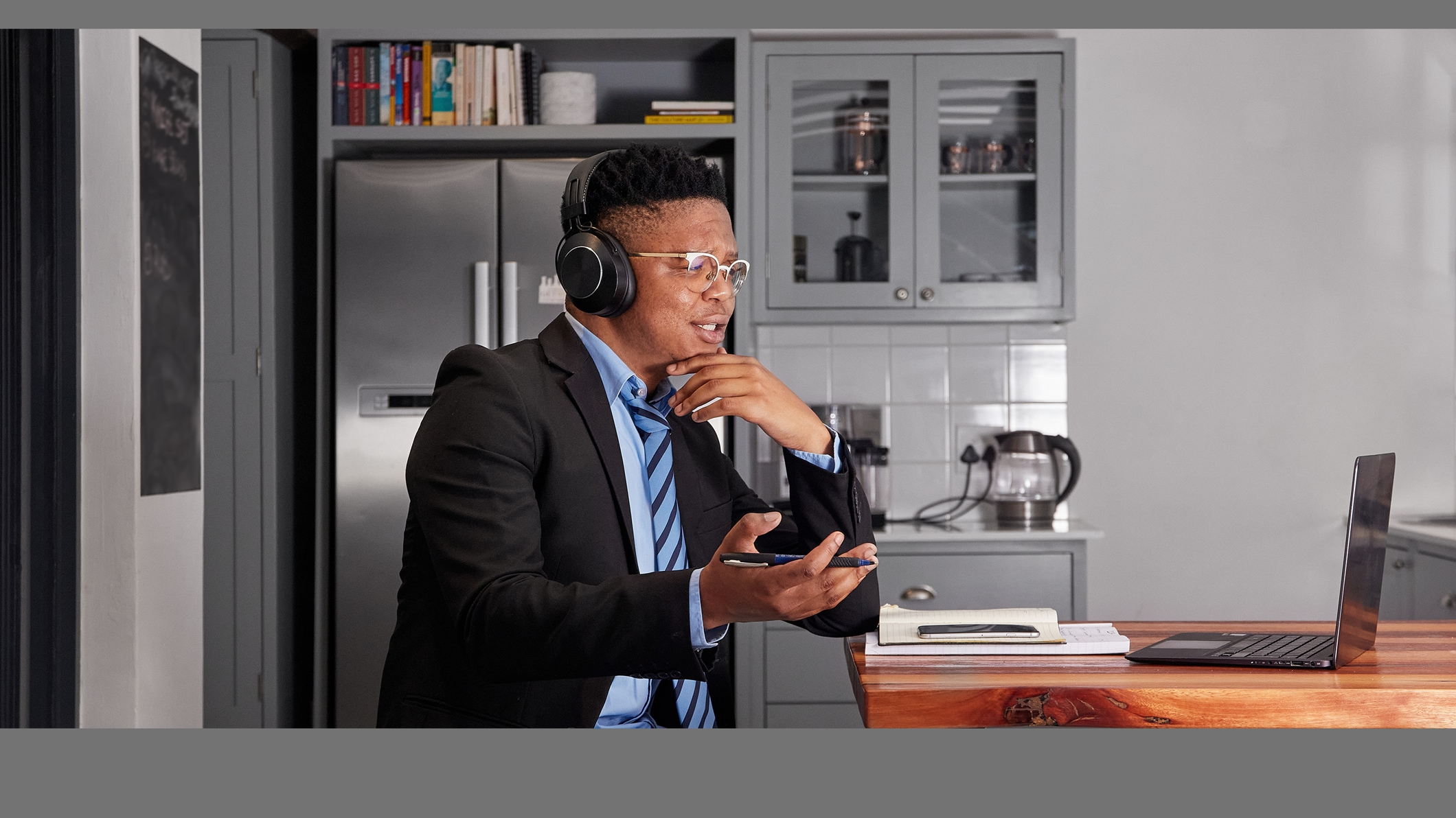 A person wearing a suit and tie using a laptop while sitting in a kitchen.