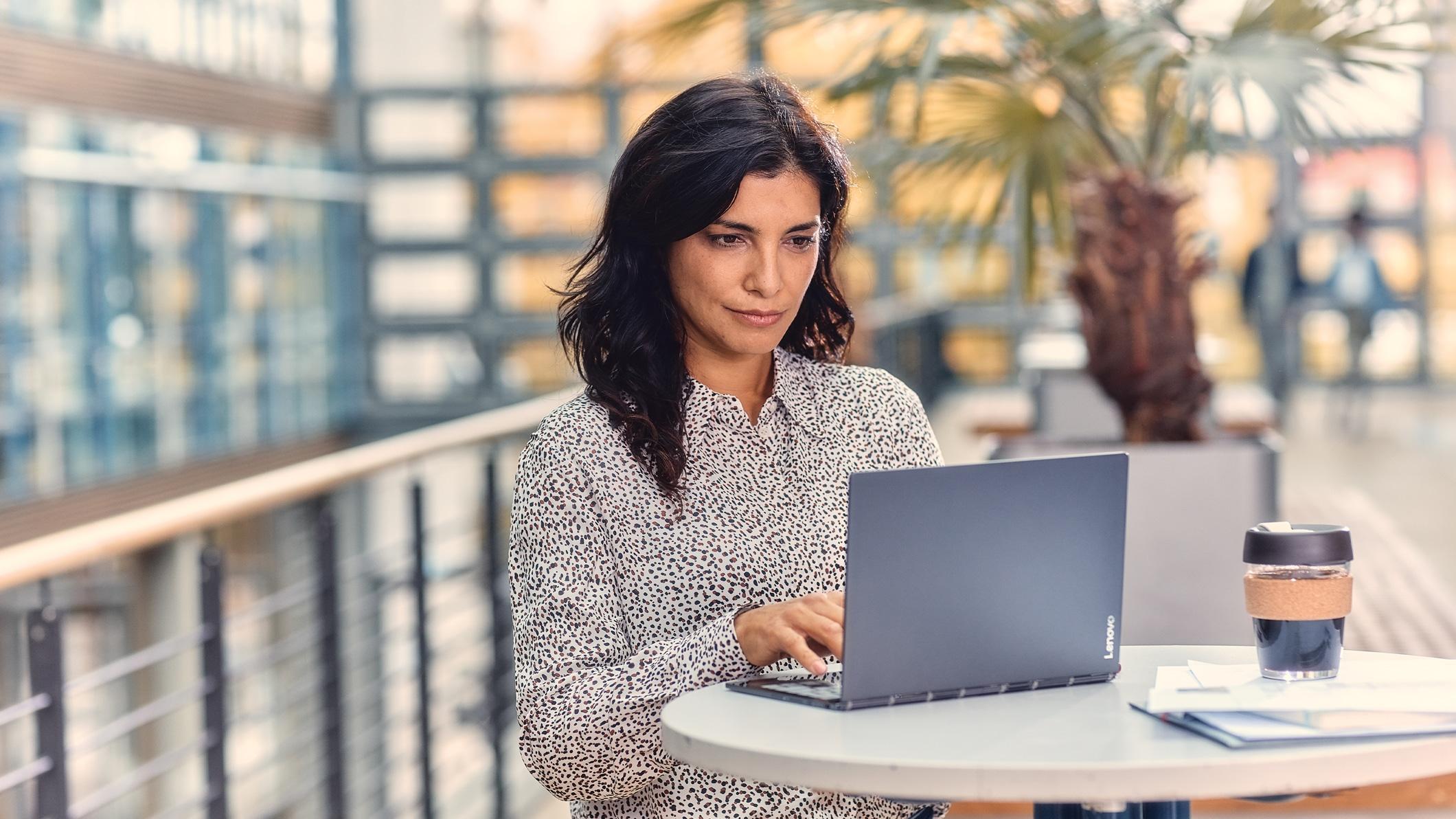 คนใช้แล็ปท็อปขณะดื่มกาแฟที่โต๊ะกลางแจ้ง